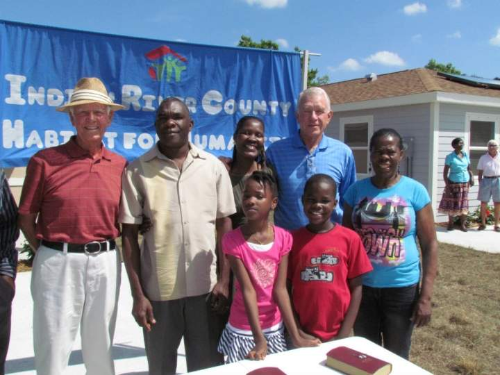 Three men, two women, and a young boy and girl standing outside at a table with two Bibles on it.