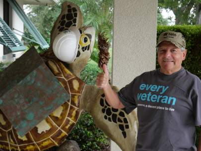 Man standing next to a sea turtle statue wearing a construction hat.